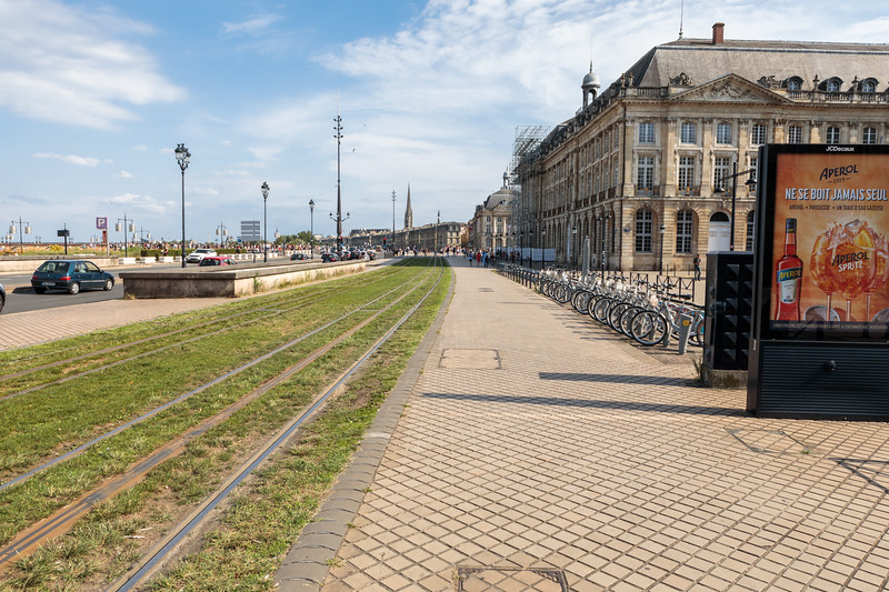 Tram rails running through grass, and a bicycle rental station by Place de la Bourse in Bordeaux, France
