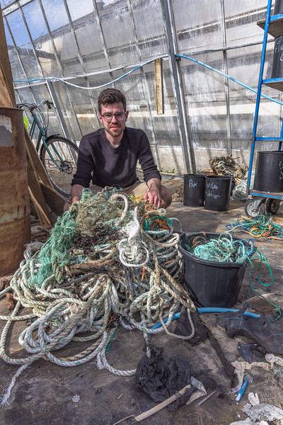 Sean Renouf sits behind a pile of rope collected from Chouet by The Clean Earth Trust volunteers on 15th May 2021