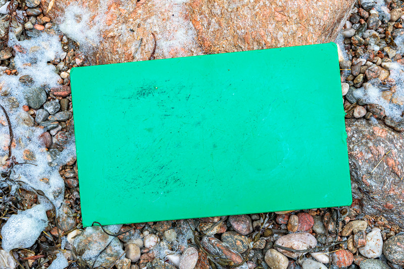 A green hard plastic cutting board on the Petit Port sea shore on Guernsey's south coast on 17th February 2020