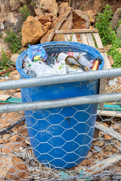 Rubbish accumulated in a blue drum behind the fence at the top of the Petit Port sea shore on Guernsey's south coast