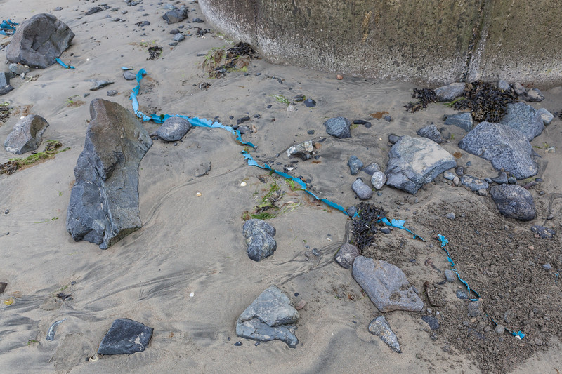 blue plastic sheet buried in the sand of Belle Greve Bay on Guernsey's east coast on 14th June 2013