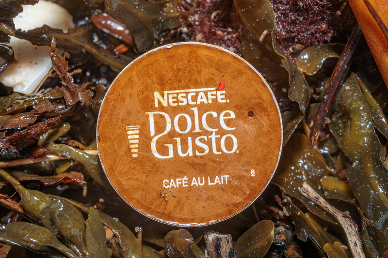 Nescafé Dolce Gusto Café au Lait capsule in the seaweed strand line at Petit Port on 20th February 2020