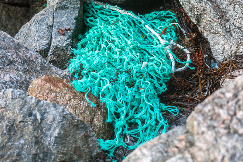 Washed up fishing net on the Petit Port sea shore