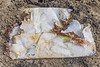 Fragmenting thick plastic bag dug out of the sand on the lower shore of Petit Port on the 28th May 2021