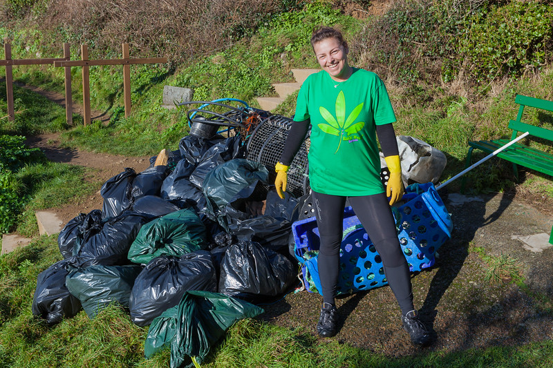 Beach clean volunteer Alicja Chrzanowska stands by bags of marine litter collected from Petit Port beach