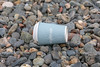 Waitrose coffee cup on the Belle Greve Bay sea shore