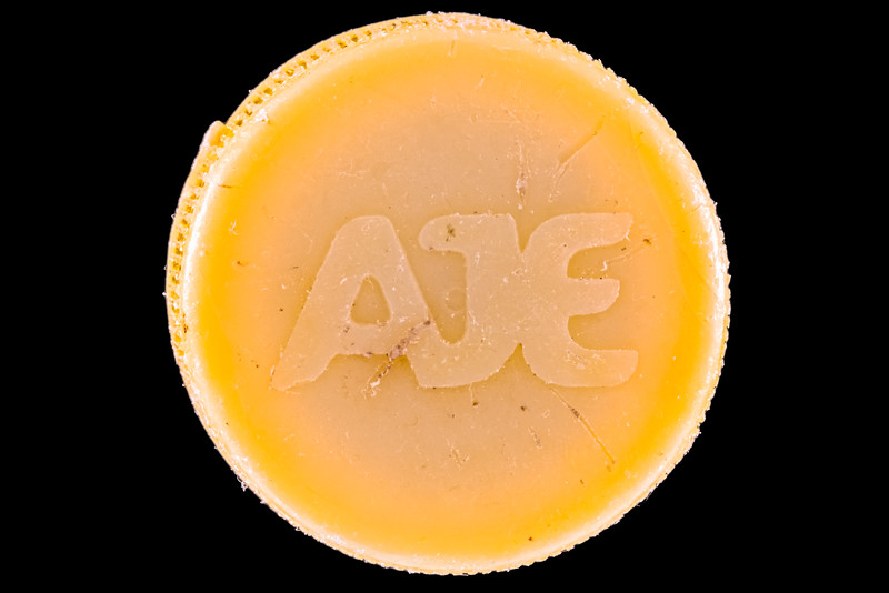 AJE Group yellow plastic bottle top collected from the Guernsey sea shore