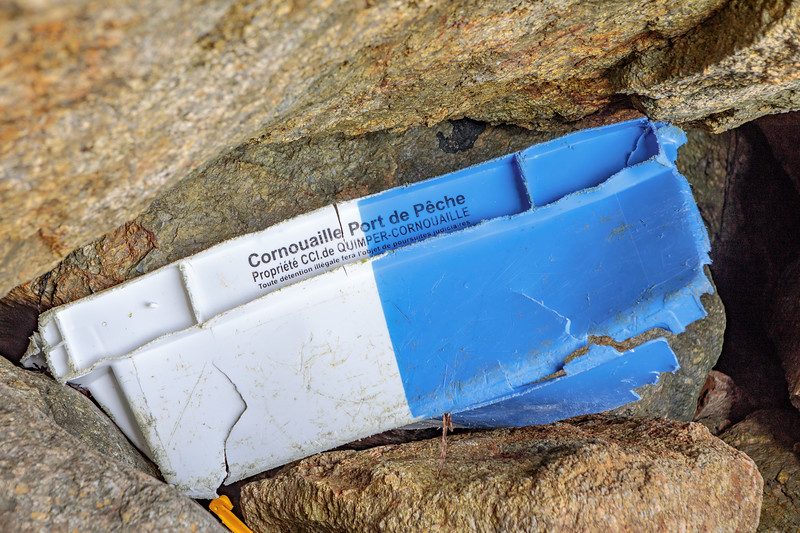 Broken fish box from Quimper Cornouaille trapped under a boulder in the sixth ravine to the west of Petit Port Beach