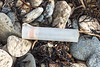 Large used plastic shotgun cartridge case on the shore of Fermain Bay on Guernsey's east coast on 11th February 2021
