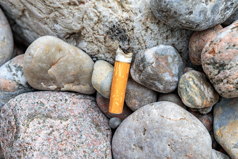 Stubbed out cigarette on the sea shore at Petit Port on Guernsey's south coast on 22nd May 2020