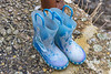 Children's boots with white socks left at Petit Port on Guernsey's south coast on the 25th March 2021