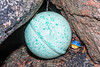 Metal float and toy trapped between two boulders on the sea shore at Petit Port on Guernsey's south coast