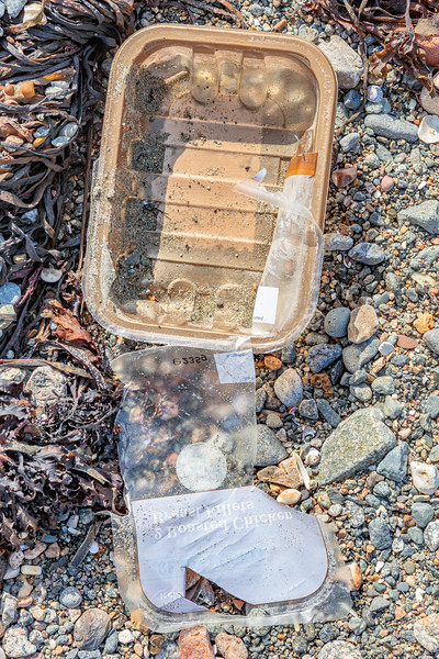 Plastic food packaging litter on the Belle Greve Bay sea shore on 21st September 2019