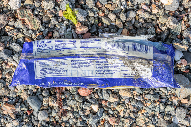 Plastic spaghetti food packaging wrapper on the Belle Greve Bay sea shore on 21st September 2019