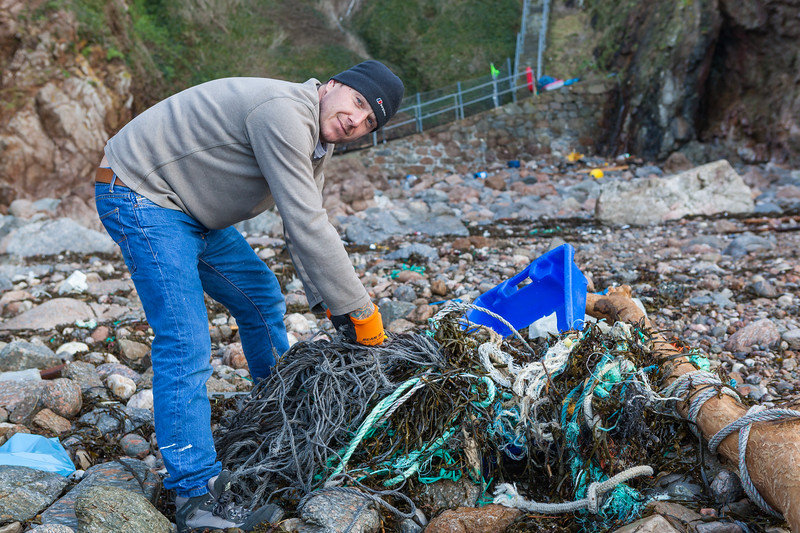 Mark Litten works to remove Nylon rope from the sea shore at Petit Port, Guernsey