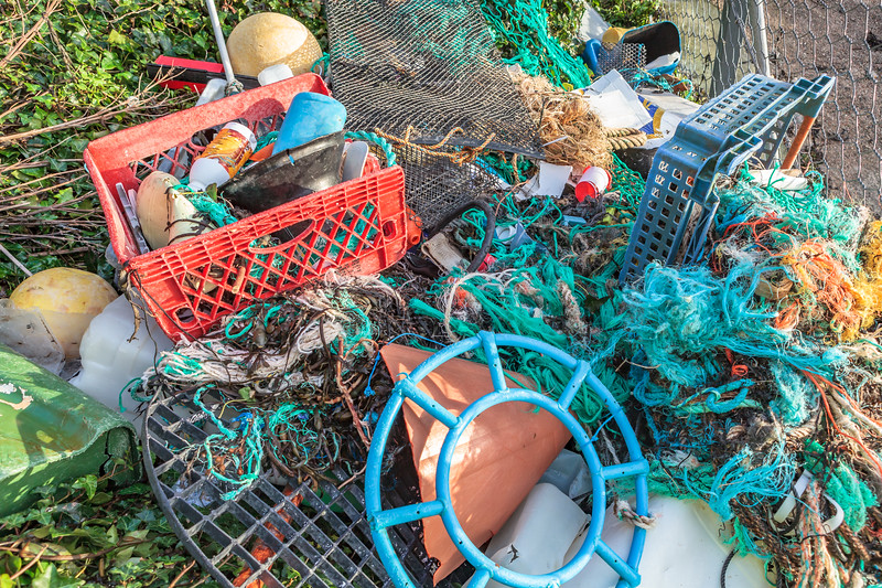 Marine plastic litter stored behind a fence at Petit Port, Guernsey waiting for collection on 16th January 2014