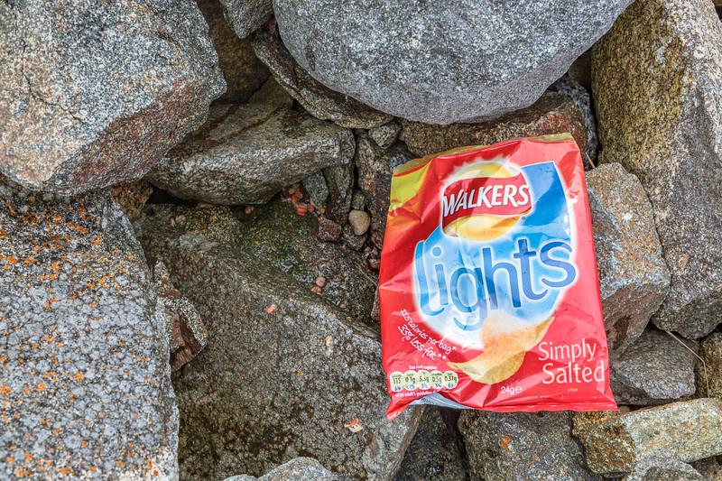 A littered Walkers crisp packet left on the sea shore kills crustaceans