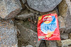 A littered Walkers crisp packet left on the sea shore kills crustaceans