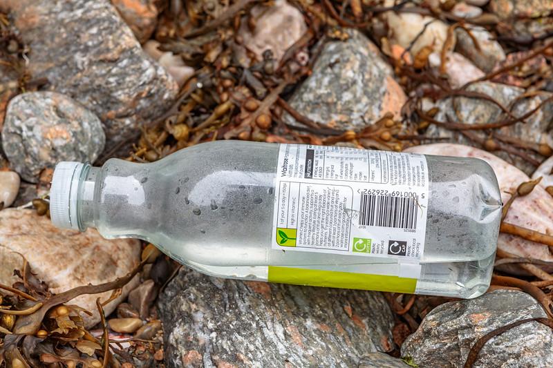Waitrose plastic water bottle on the Petit Port sea shore on 8th July 2020
