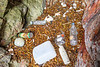 Polystyrene pieces, plastic bottles and containers, a metal float and a metal can stranded in a cave at the top of the Petit Port sea shore on 1 October 2019