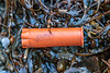 Plastic shotgun cartridge case washed up on the seaweed strand line at Petit Port on  28th November 2019