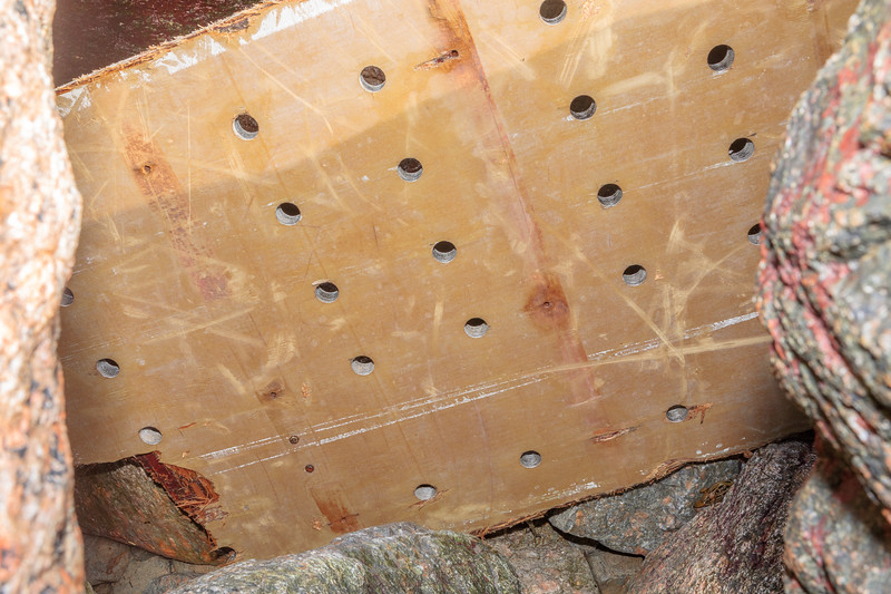 Piece of wood floor of ship's refrigeration unit wedged between boulders at Petit Port on 26th February 2020