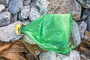 Crushed green plastic Sprite bottle on the Pleinmont sea shore on Guernsey's south west coast on 5th February 2021