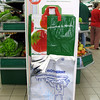 In an effort to reduce the use of one-use disposable plastic carrier bags many supermarkets offer reusable bags.  This image shows a display of reusable grocery bags at a supermarket in Bayeux, Normandy.  Many jurisdictions around the world are banning the use of disposable plastic carrier bags, which are detrimental to the environment.  Plastic carrier bags can blight our countryside.  Some enter the sea where they pose a threat to wildlife.  They have been responsible for the death of turtles and cetaceans that consume them by mistake.  Degraded plastic enters our food chain as microscopic particles.<br /> <br /> Bayeux shopping bags 040807 9917