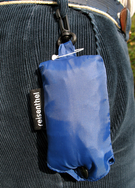 REDUCING PLASTIC CARRIER BAG OR SACK USE: <br /> <br /> This small pouch which contains a very strong folded polyester bag is ideal for people, and for in men in particular, who habitually forget to bring a shopping bag with them when they pop into a convenience store or a supermarket to purchase a few items.  The pouch clips onto a belt loop.  I  have one clipped to one of my trouser belt loops so I carry one with me at all times.  I forget I have it until I need to use it.  It has stopped me using countless single use plastic carrier bags.  These reusable bags are made by Reisenthel Accessoires, which is a German company.  This product called a Mini Maxi Shopper can be purchased in retail shops  in Belgium, The Netherlands and Germany for about 4.95 euros.  I saw them for sale in New York City in the summer of 2007 where they were $7.95 without sales tax.<br /> File No. 111007 1301<br /> ©RLLord<br /> fishinfo@guernsey.net