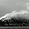 Svalbard scenery in monochrome.  The cloud formation and the light make the mountain appear to be on fire.