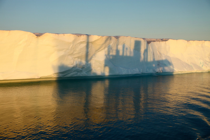 The ice front of Brasvelbreen as the sun set with the shadow of the M/S Stockholm