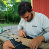 Trek instructor Derek Breaux carves his name into a piece of driftwood found on Island Outpost in Lake Fausse Pointe State Park near Loreauville, LA, Thursday, July 3, 2014. <br /> <br /> Paul Kieu, The Advertiser