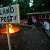 The hide of a water moccasin snake is draped over a welcome sign as counselors of the Swamp Base program converse near a campfire on Island Outpost in Lake Fausse Pointe State Park near Loreauville, LA, Thursday, July 3, 2014. <br /> <br /> Paul Kieu, The Advertiser