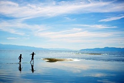 The kids run through the shallows of the Great Salt Lake, hoping from island to island