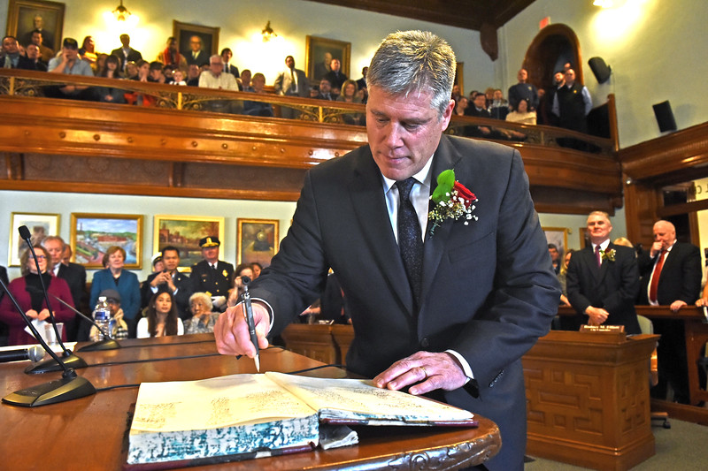 The Mayor for Lowell John J. Leahy, signs the City Ledger after being sworn In. SUN/ David H. Brow