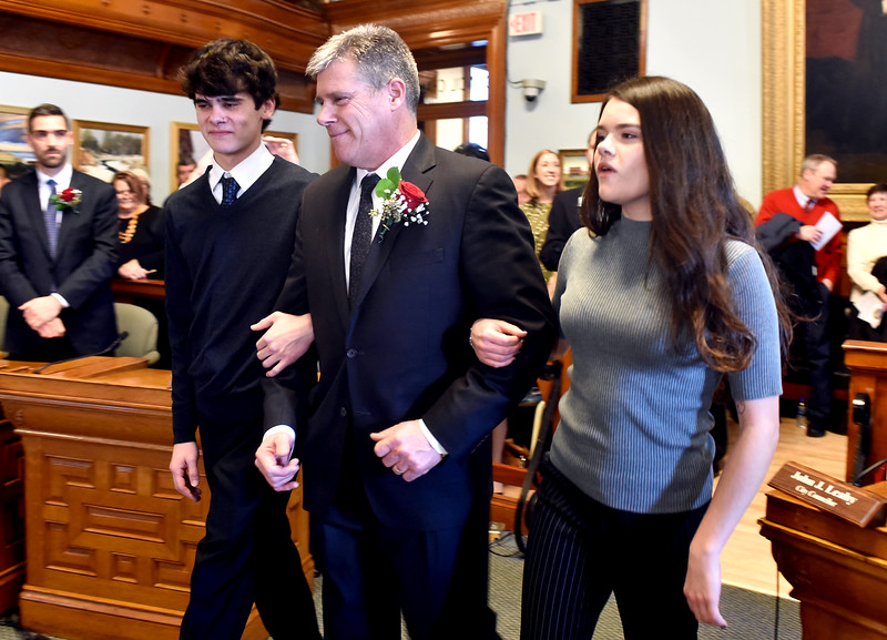 The newly elected Mayor of Lowell John J. Leahy is esored by two of his children from Left Jack Leahy 19 and Madeline Leahy 21, to be sworn in as Mayor. SUN/ Dvid H. Brow