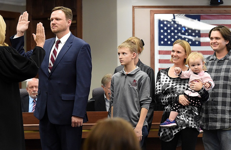 Jeremy Jersvig, left, Loveland's new ward 1 city councilor, is sworn in by Judge Geri Joneson, far left, Tuesday, Nov. 14, 2017, as his family watches at the municipal building in downtown Loveland. His family from left are son, John, 13, daughter, Taylor, 16, (behind John) wife, Brittiany, daughter, Shayla, 1, and nephew, Chaz.  (Photo by Jenny Sparks/Loveland Reporter-Herald)