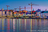 The Gamla Stan waterfront skyline with construction cranes at night in Stockholm, Sweden.
