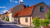 A street view with homes and buildings featuring the architecture of Visby, Sweden.