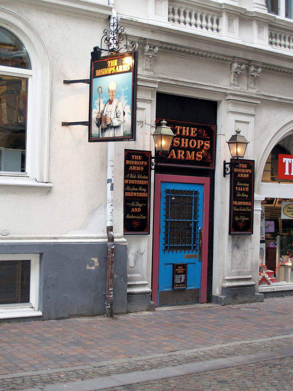 """A pub in Helsingborg. Note the bottom of the left sign where it says """"No Dogs and Mothers-in-Law""""."""
