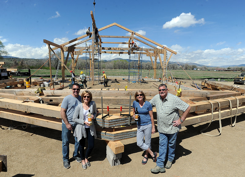 The owners of Sweetheart City Wines pose for a photo as a crew works to construct a timber frame building to house the winery Monday, April 25, 2016, west of Loveland. From left are David Burks, Kathy Burks, Jack Cantley and Lindsay Cantley. (Photo by Jenny Sparks/Loveland Reporter-Herald)
