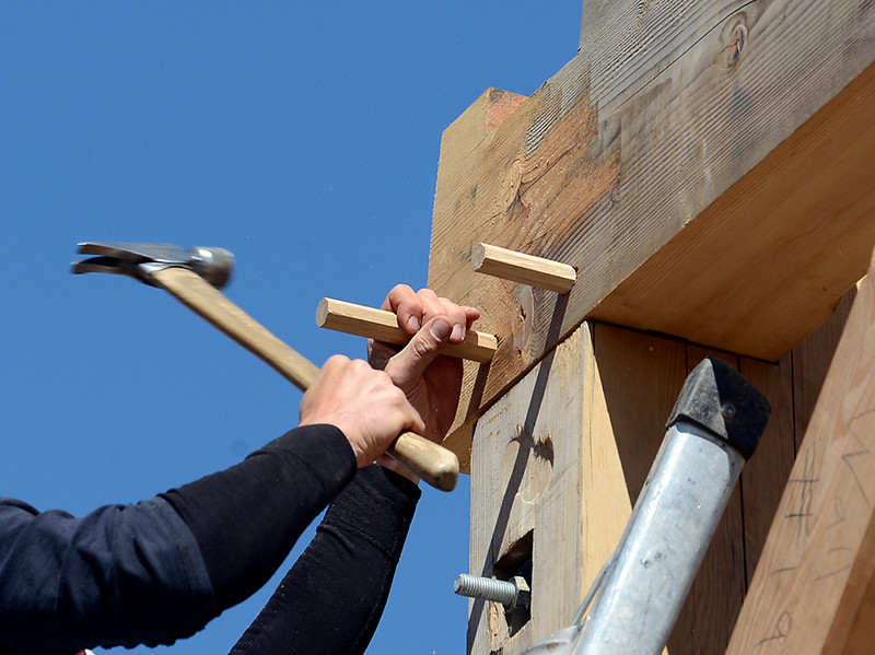 Cody Koelliker pounds wooden pegs into timbers as he and a crew to construct a timber frame building Monday, April 25, 2016, west of Loveland. The unique building will be home to Sweetheart City Wines. (Photo by Jenny Sparks/Loveland Reporter-Herald)