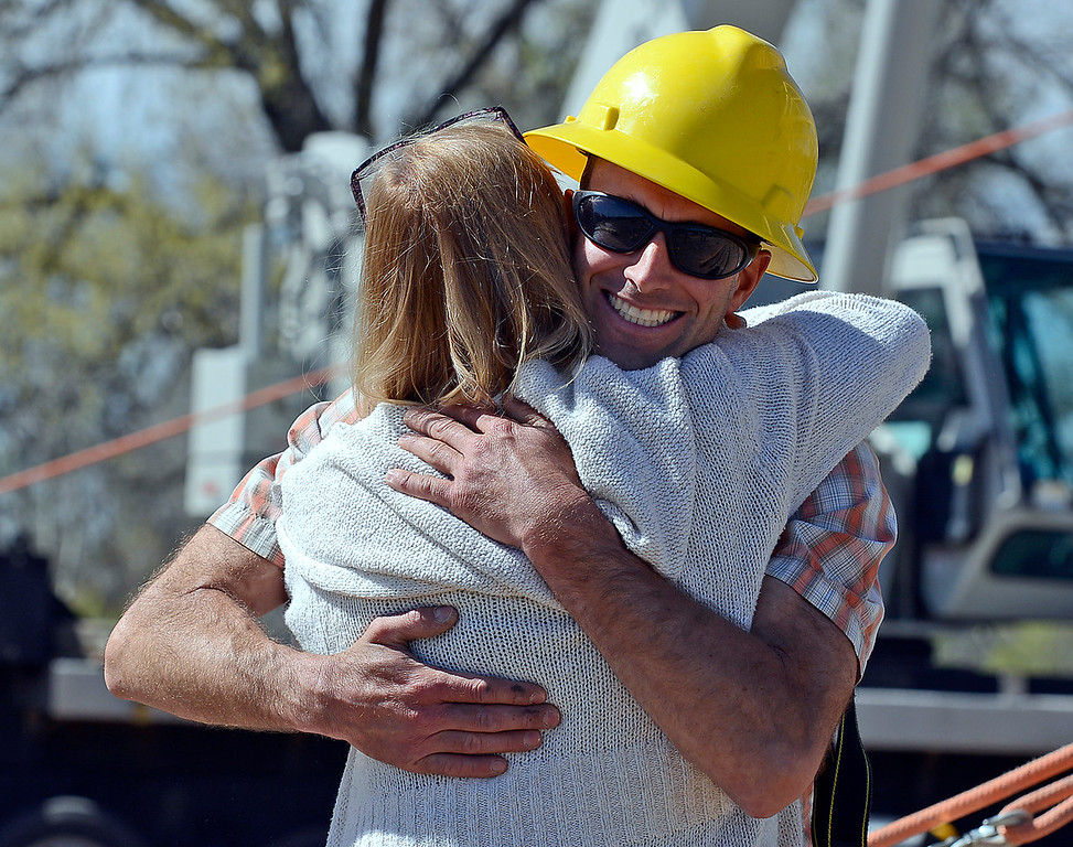 Andy Johnson, owner of Powder Cache Designs, hugs Kathy Miller as a crew works to construct a timber frame building Monday, April 25, 2016, west of Loveland. Kathy's husband Mark Miller, who died in August 2012, cut and notched the wood to build a shop for his business, Trail Ridge Timber Frames, but sold it to the owners of Sweetheart City Wines. Kathy watched as the crew worked to assemble the timber building her husband labored over years ago. (Photo by Jenny Sparks/Loveland Reporter-Herald)