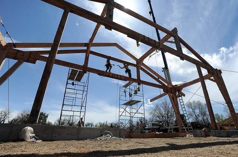 Ethan Smith, right, hands a tool to Nathan Long, left, while working with a crew to construct a timber frame building Monday, April 25, 2016, west of Loveland. The unique building will be home to Sweetheart City Wines. (Photo by Jenny Sparks/Loveland Reporter-Herald)