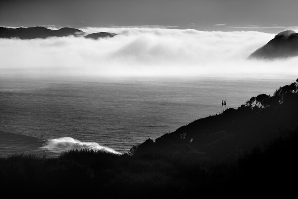 View over Manu Bay point break with surfers and wave in foreground, with morning fog rising up in the Whaingaroa Harbour. New Zealand 2014 https://art.tt/8px