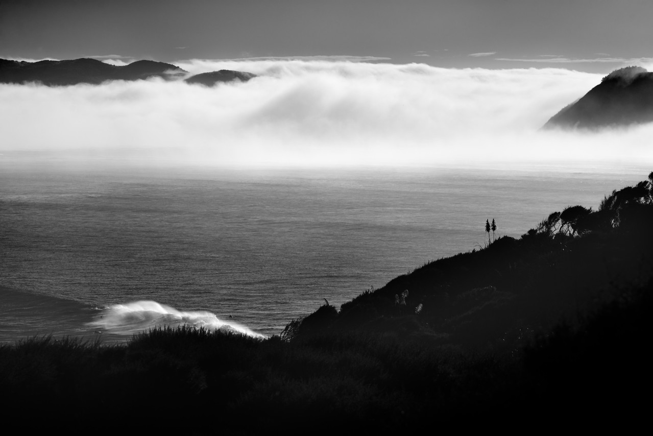 "View over Manu Bay point break with surfers and wave in foreground, with morning fog rising up in the Whaingaroa Harbour. New Zealand 2014 <a href=""https://art.tt/8px"">https://art.tt/8px</a>"