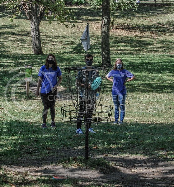 Looking uphill to the target, junior Lina Parks, Micah Sapp and Morghan Caldwell calculate their upcoming throws.<br /> Photo By Macey Franko
