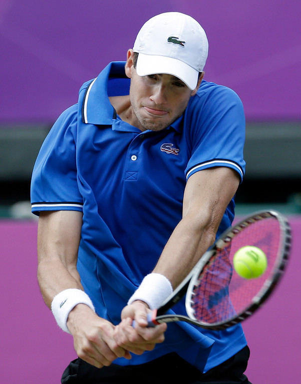 John Isner of the United States returns to Roger Federer of Switzerland at the All England Lawn Tennis Club in Wimbledon, London at the 2012 Summer Olympics, Thursday, Aug. 2, 2012. (AP Photo/Elise Amendola)