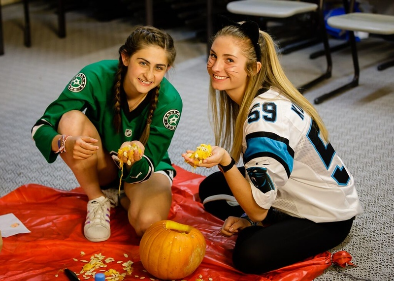 Hanna and McAuley cleaning out a pumpkin during Halloween