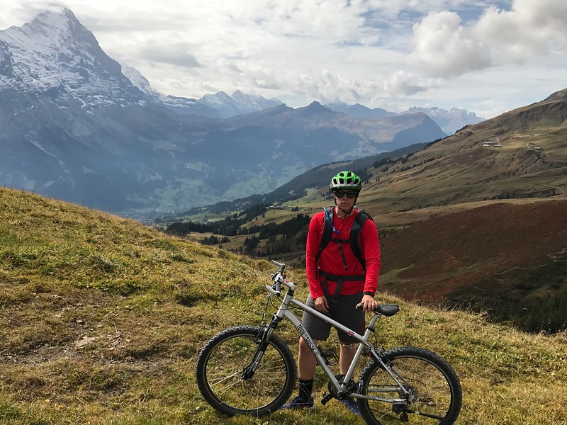 Sam, not smiling for the camera:) (Grindelwald down below and Kleine Scheidegg Pass behind where we had biked over earlier in the morning)